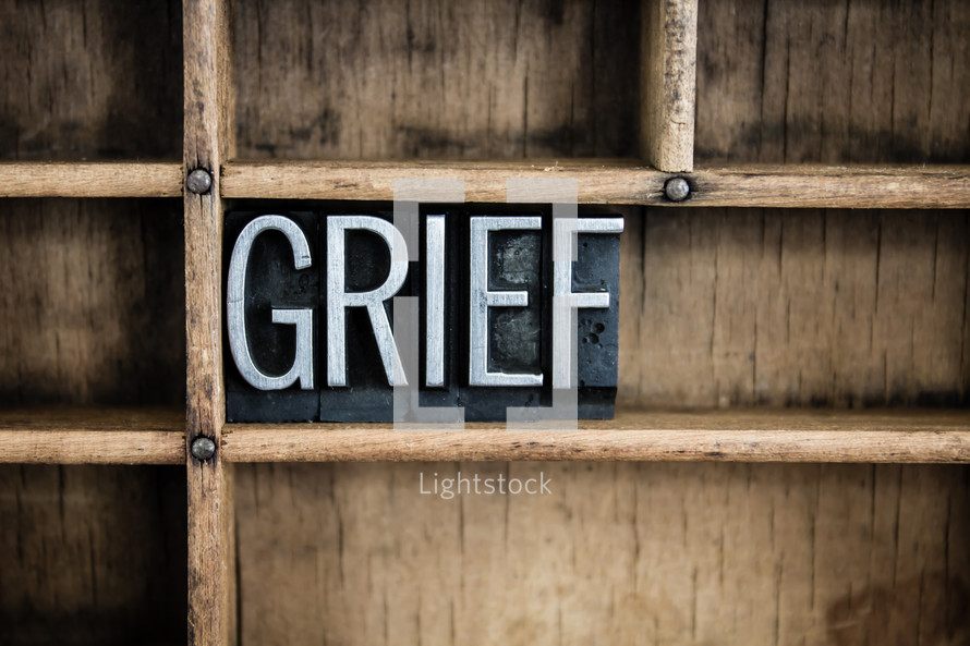 word grief in blocks on a bookshelf