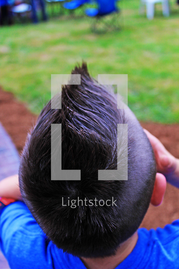 Back of a boy's head with fun hair style, outside playing hide and seek with friends in summer.