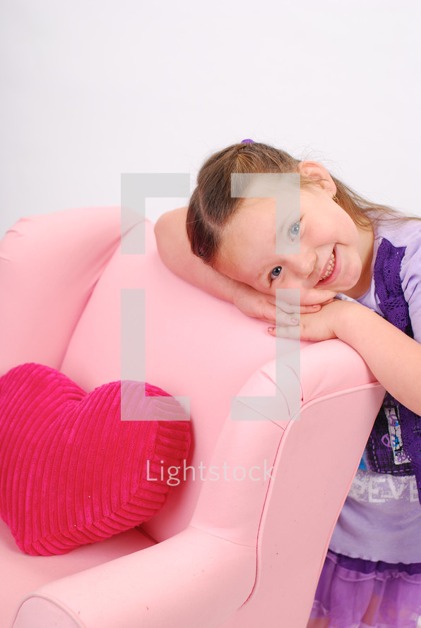 girl child resting her head on a pink recliner