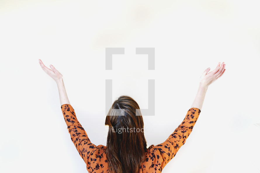 a woman looking up with hands raised