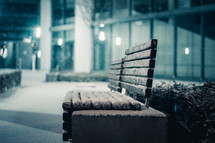 snow on a bench at night