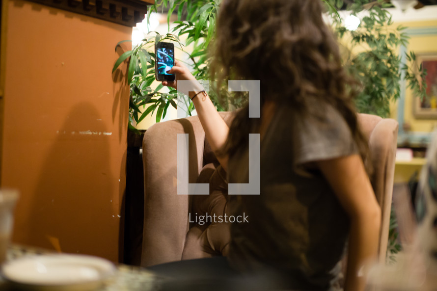 Girl sitting in a cafe taking a picture with her cell phone.