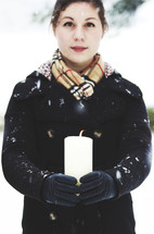 a woman holding a candle and falling snow