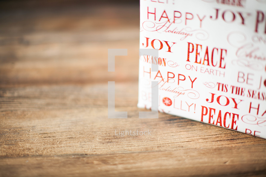 A Christmas present on a wood table - Peace and joy - wrapping paper