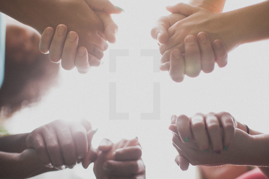 holding hands in a prayer circle - unity