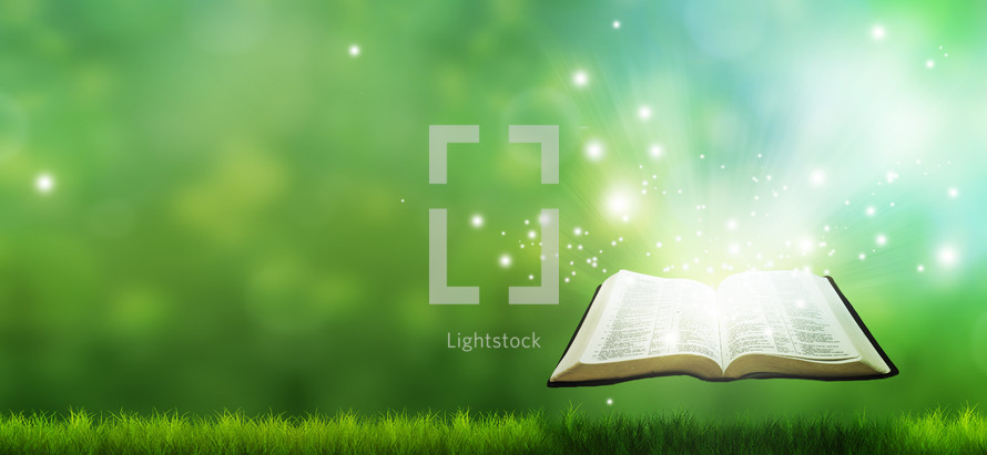 glowing Bible releasing sparks over grass