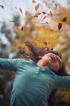girl throwing fall leaves