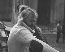 a man playing a cello on the streets of Rome