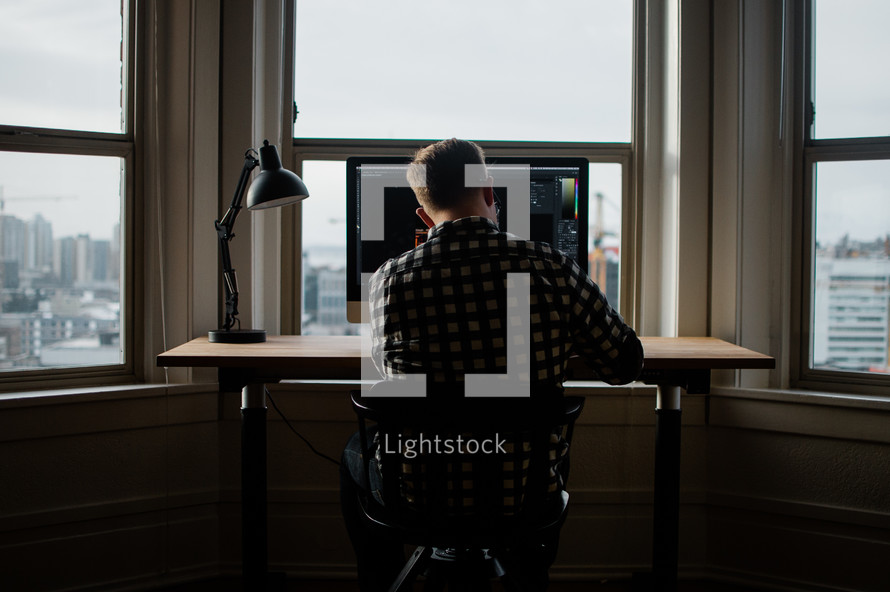 a man sitting in front of a computer screen