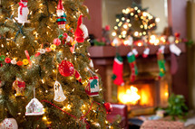 ornaments on a decorated Christmas tree and a hearth