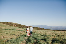 a couple walking holding hands on a mountaintop