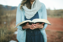 woman holding an open Bible outdoors