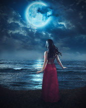 woman in a red dress looking at a full moon