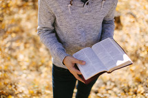 man standing holding a Bible in fall leaves