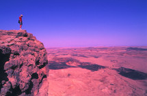 Man standing on a mountain cliff overlooking harsh desert terrain