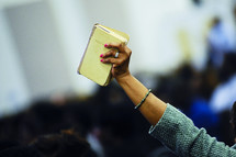 A woman holding up a hymnal