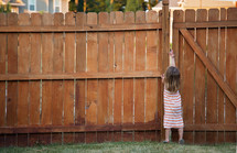 a child opening the latch of a gate