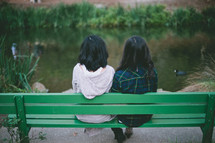 friends sitting on a bench outdoors talking