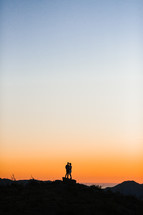 silhouette of a couple against an orange sky