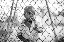 a child looking through a chain link fence