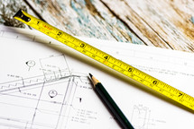 tape measure, blueprints, and pencil
