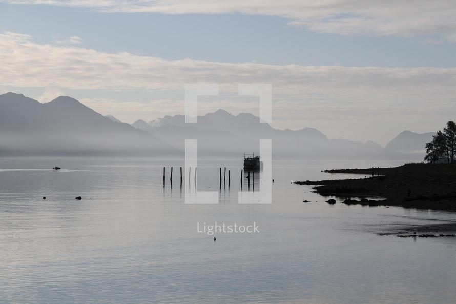 fishing boat over a foggy lake