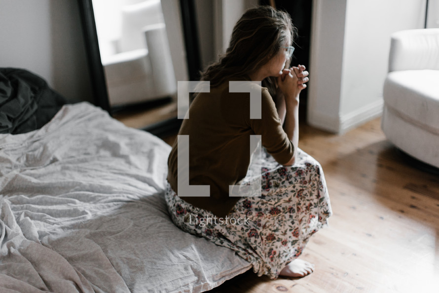 a woman sitting at the edge of a bed praying
