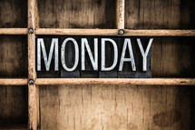 word Monday in blocks on a bookshelf