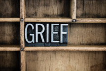 word grief in blocks on a bookshelf