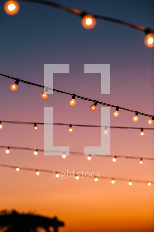 string of lights against an orange sky at sunset