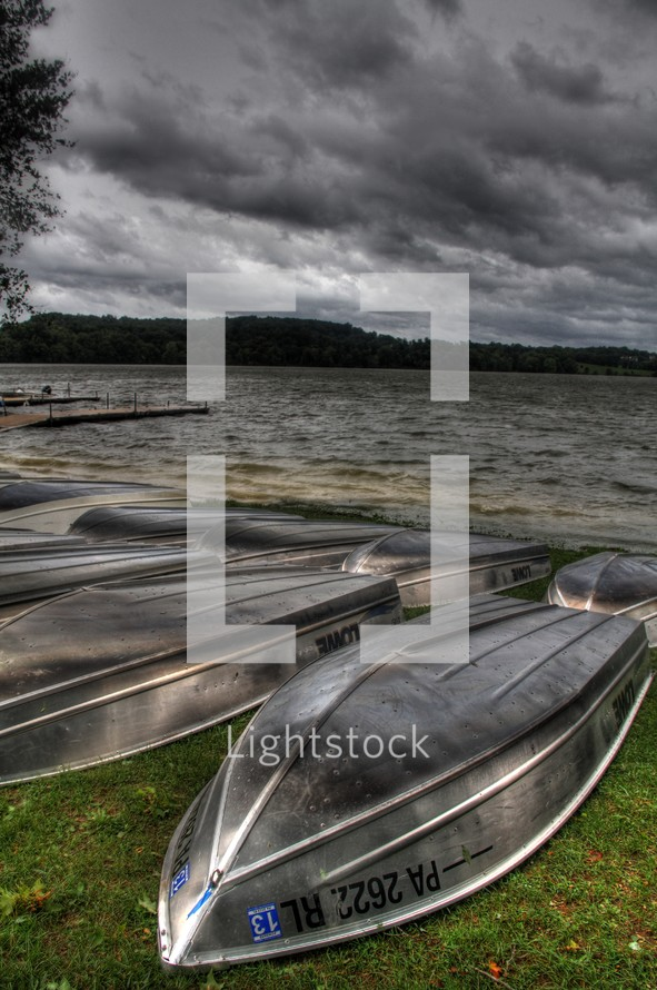 flipped rental boats resting on a lake shore as storm clouds approach