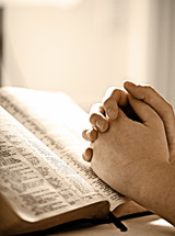 Prayer hands on top of open Bible.