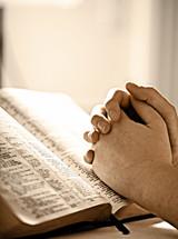 Prayer hands on top of open Bible.