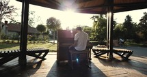 man playing a piano outdoors