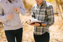 men standing together discussing a Bible on a fall day