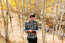 a man standing alone in a forest reading a Bible