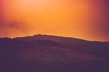 mountaintop under an orange sky