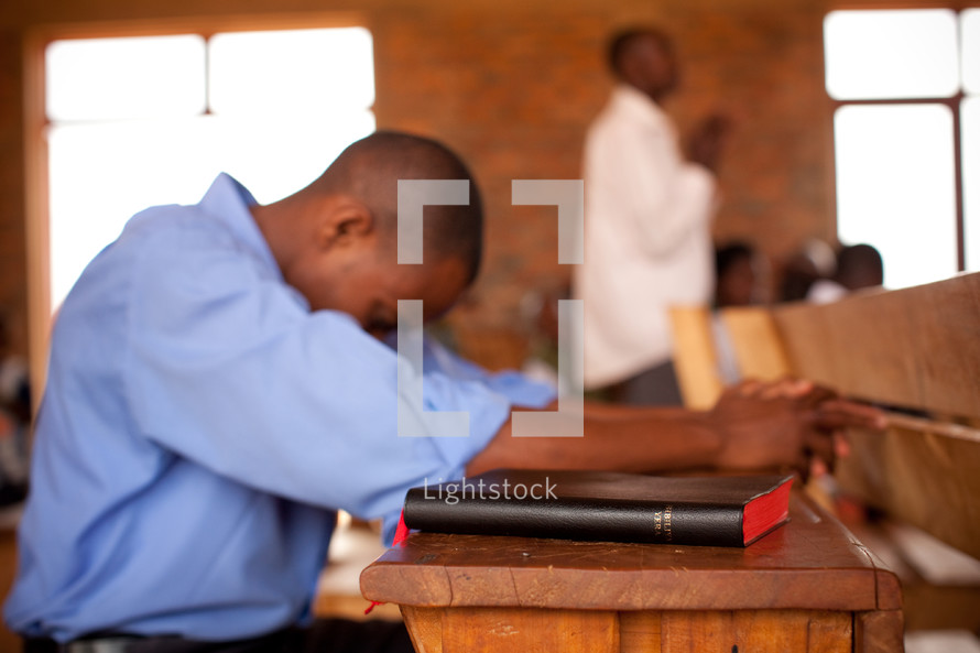 a man in Africa with his head bowed in prayer in a church