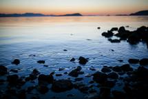 rocks along a shore at sunset