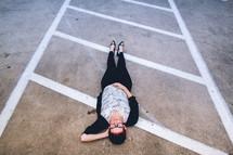 woman lying in a parking lot