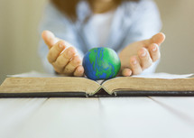 a woman holding a globe over the pages of a Bible