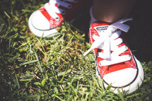 red sneakers on a toddler standing in the grass
