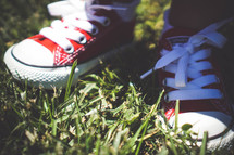 red converse sneakers on a toddler standing in the grass
