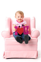 toddler sitting on a pink recliner holding an I heart you sign
