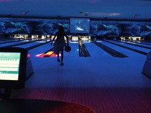 a girl bowling at a bowling alley