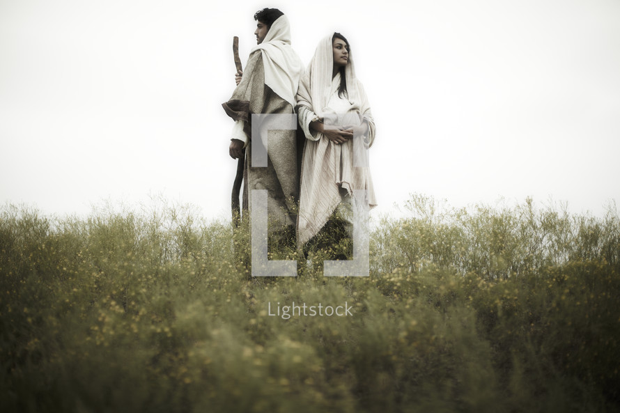 pregnant Mary and Joseph standing back to back in a field