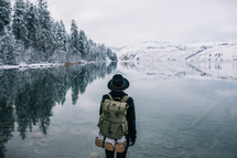 a woman backpacking near a snowy lake shore