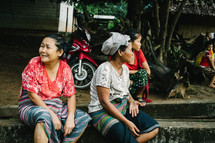women sitting on a concrete curb waiting