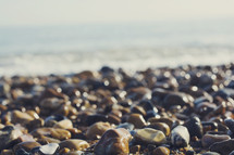 The Eastbourne coast, in the south of the UK. Beautiful autumn weather. Not a sandy beach, but full with little stones and rocks, near the white cliffs of Dover. Beautiful sunlight shining on wet rocks.