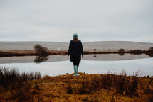 a woman in rain boots standing at the edge of a pond